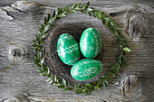 Hand-painted green Easter eggs in wreaths of box and willow