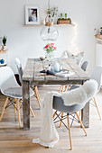 Grey and white shell chairs around rustic, shabby-chic wooden table