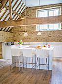 Open-plan kitchen below exposed roof structure in converted barn