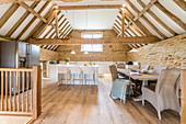 Open-plan kitchen and dining area below exposed roof structure in converted barn