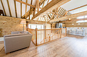 Open-plan interior below exposed roof structure in converted barn