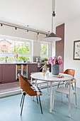 Various chairs around table in front of kitchen counter with dusky-pink cabinets