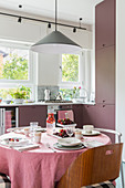 Set table in kitchen-dining room with dusky-pink cabinets