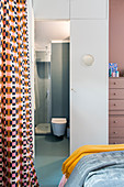 Small ensuite bathroom with door surrounded by cupboards