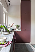 L-shaped kitchen counter with claret-coloured cabinets