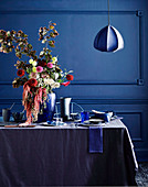 Laid table in shades of blue with a lush bouquet of flowers, pendant lights above