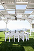 White table on roof terrace with artificial lawn and solar panels on pergola