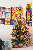 Christmas tree and presents in corner below comic-style artworks on wall