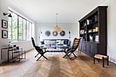Dark bookcase, chairs, coffee table and sofa in living room with herringbone parquet floor