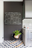 Chalkboard panel on black wall and classic rocking chair next to kitchen cupboards