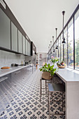 Long, narrow kitchen with concrete counter, cement tiles and glass wall