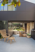 Rattan chair on concrete terrace with roofed dining area in background