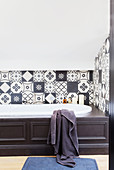 Bathtub with dark wood panelling in bathroom with black-and-white wall tiles