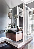 Countertop basin on an elegant washstand, above it an oriental pendant lamp