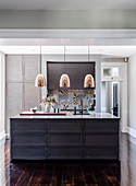 Kitchen island with marble top, copper pendant lights above it, colorful tiles in the background as splash protection