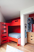 Red bunk beds in modern boys' bedroom with sloping ceiling