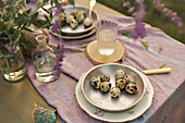 Quail eggs on plates on set table