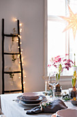 Festively set table and ladder decorated with fairy lights