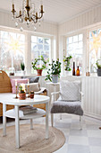 Round table, armchair, wooden bench and houseplants in Scandinavian-style conservatory