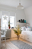 Teenager's bedroom with white wood cladding decorated for Christmas