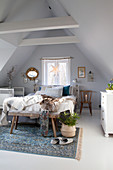 Double bed, cot and rustic wooden bench in attic bedroom