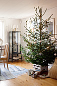 Decorated Christmas tree and gifts in front of display cabinet in living room