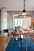 Wreath hung above table set for Christmas dinner in dining room with tiled stove