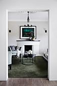 Eleganter Kamin, davor Polstersessel und Couchtisch im Wohnzimmer
