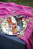 Tea glasses and silver teapot on tray with leafy twigs