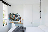 Double bed, pendant lamp, built-in wardrobe, small desk and photo gallery on the wall in a white bedroom
