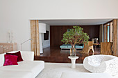 Weißer Designer-Sessel in Häkel-Look, Blätterzweig auf Beistelltisch und weißes Sofa in offenem Wohnraum vor Durchgang