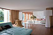 Türkisfarbene Liege, Designer-Stehleuchte und Rattanmöbel, im Hintergrund Lounge