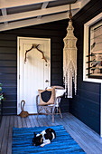Chair in front of white door, macrame chandelier and dog on blue carpet on wooden veranda