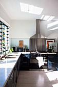 L-förmige Küche mit Lichteinfall durch Lamellenfenster