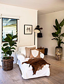 Day bed with white cover, floor lamp and house plants in the living area