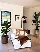 Tagesbett mit weißer Husse, Stehlampe und Zimmerpflanzen im Wohnbereich