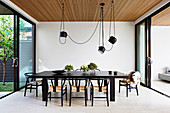 Dark dining table with classic chairs and pendant lights above the patio door