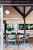 Open kitchen with light wooden front and mirrored back wall, in the foreground dining table with green upholstered chairs