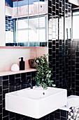 Weißes Wascchbecken und Spiegelschrank im Badezimmer mit schwarzen Wandfliesen