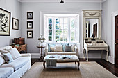 Classic living room with sofa in the bay window and antique secretary