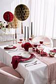 Festlich gedeckter Tisch in Rosa und Weiß mit Wabenbällen als Deko