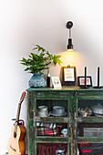 Vase of leafy branches, pictures and candles on top of green cabinet below wall-mounted lamp