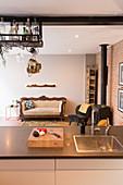 Blick über Küchentheke auf Kaminofen, Retro Sessel, Holzlager und Sofa in offenem Wohnraum mit Ziegelwand