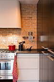 Dunstabzugshaube über Küchenzeile an Ziegelwand und Einbauschrank