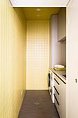 Waschraum mit gelben Wandfliesen