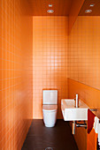 Gäste-Toilette mit orangefarbenen Wandfliesen