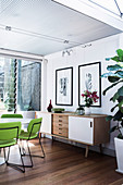 Lime green chairs around white table and sideboard in open dining area