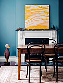 Wooden table with chairs in front of a fireplace, modern art in yellow tones on a mantelpiece
