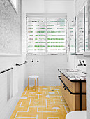 Vanity in front of shower and louvre window in bathroom with yellow and white tiled floor