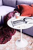 Cup and book on designer table on sofa with plaid in berry tones